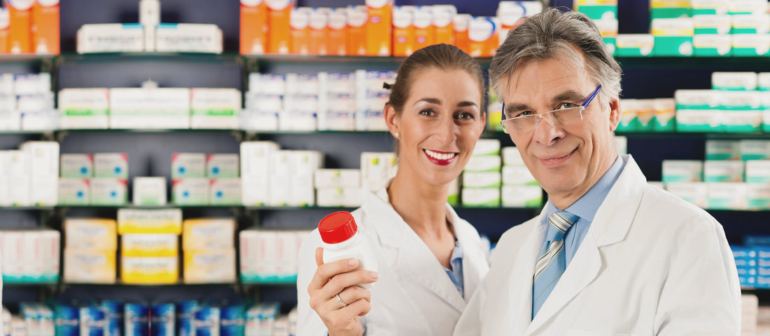 an old man pharmacist holding bottle medicine with young lady pharmacist