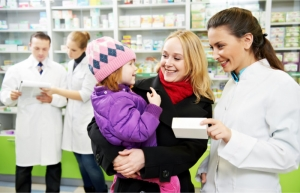 mother and pharmacist listening to a child and other pharmacists are on the background