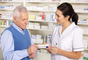 pharmacist showing the senior a box of medicine tablets